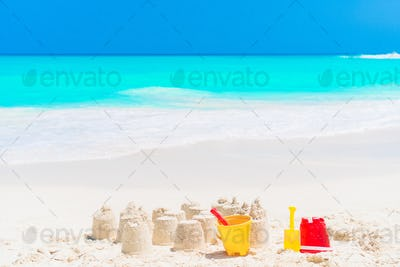 Sandcastle at white beach with plastic kids toys and sea background