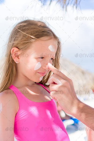 Father applying sun cream to daughter nose. Portrait of cute girl in suncream