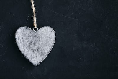 Valentines Day background with heart. Homemade wooden rustic heart on dark blackboard
