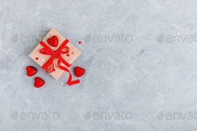 Valentine Day background with red hearts and a gift box with red ribbon.