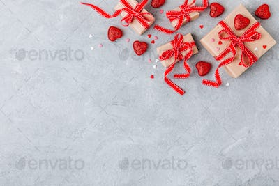 Valentine Day background with red hearts and a gift boxes with red ribbons.