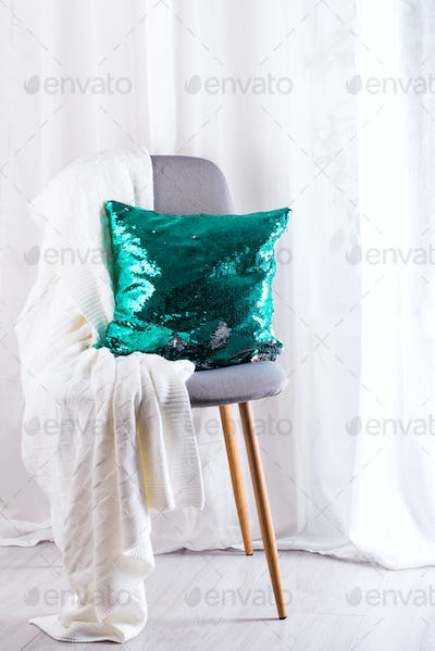 White plaid and green sequins pillow on gray armchair over window of living room