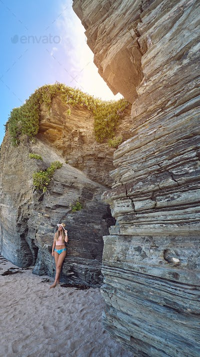 Young woman with a hat enjoying summer on a beach full of cliffs and rocks in Galicia