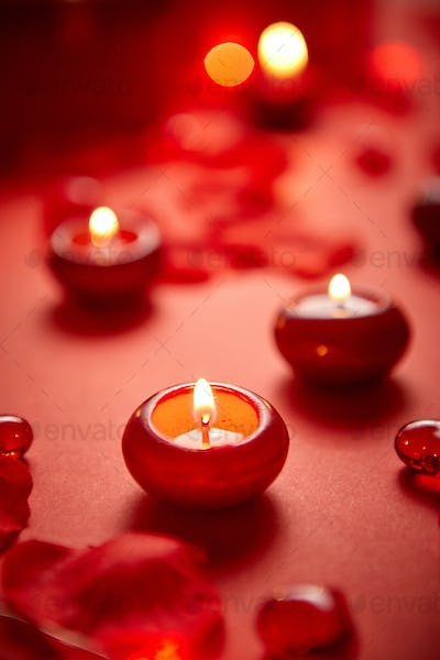 Romantic dinner decoration. Red candles, flower petals, on the table