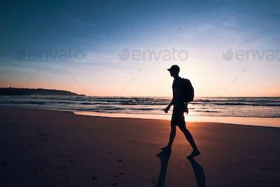 Traveler on beach at sunrise