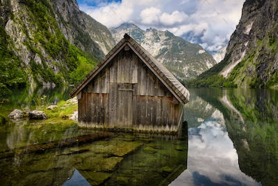 Old wooden cabin in alpine Lake Obersee