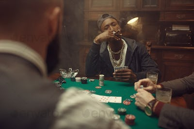 Poker players at gaming table with green cloth