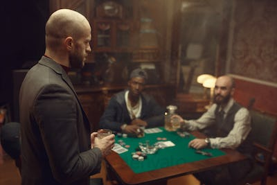 Three poker players with whiskey and cigars