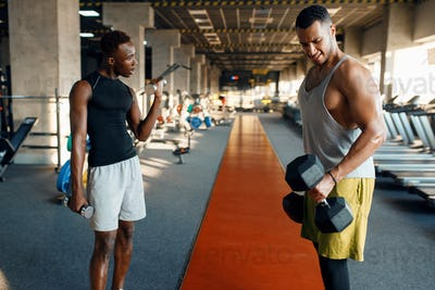Two tired athletes doing exercise with dumbbells