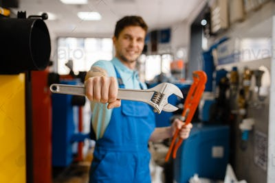 Plumber shows pipe wrenches in plumbering store