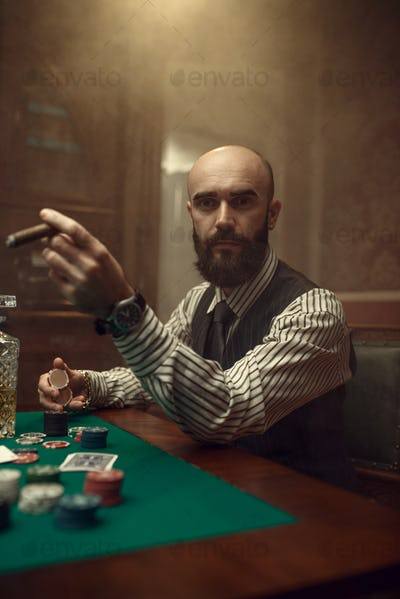 Bearded poker player with cigar playing in casino