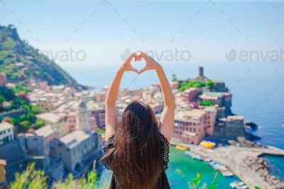 Beautiful girl making with hands heart shape on the old coastal town background of Vernazza, Cinque
