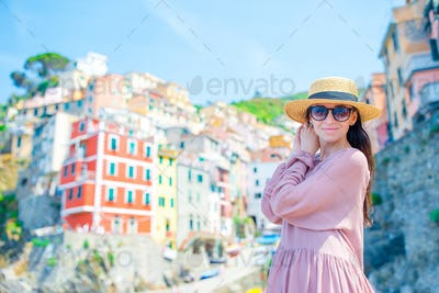 Young woman with great view at old village Riomaggiore, Cinque Terre, Liguria, Italy. European