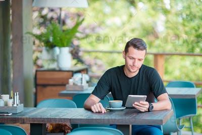 Young man with laptop in outdoor cafe drinking coffee. Man using mobile smartphone