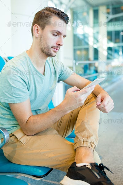 Young man in an airport lounge waiting for flight aircraft. Caucasian man with smartphone in the