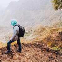 Santo Antao Island, Cape Verde. Traveler with backpack on hiking stony path enjoying view of surreal