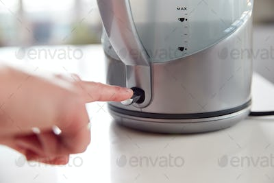 Close Up Of Woman Pressing Power Switch On Electric Kettle To Save Energy At Home