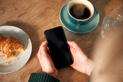 Close Up Of Woman Looking At Blank Screen With Copy Space On Mobile Phone  In Cafe
