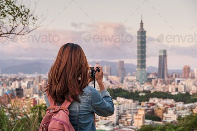 Young woman traveler taking photo of beautiful cityscape