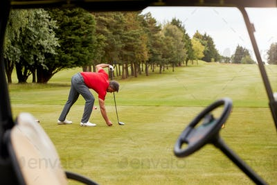 Mature Male Golfer Preparing To Hit Tee Shot Along Fairway With Driver Viewed Through Buggy Window