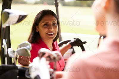 Two Women Playing Golf Driving Buggy And Talking Over Clubs