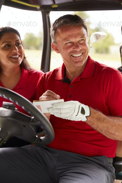 Mature Couple Playing Golf Marking Scorecard In Buggy Driving Along Course