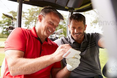 Two Mature Men Playing Golf Marking Scorecard In Buggy Driving Along Course