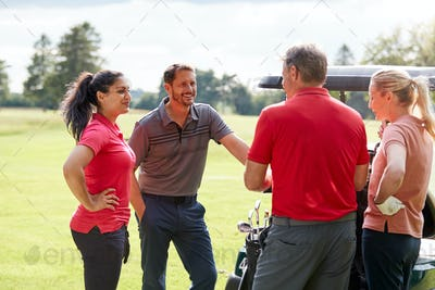 Group Of Male And Female Golfers Standing By Golf Buggy On Course