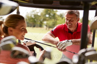 Couple Playing Golf Driving Buggy And Talking Over Clubs