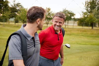 Two Mature Men Playing Round Of Golf Carrying Golf Bags Along Fairway