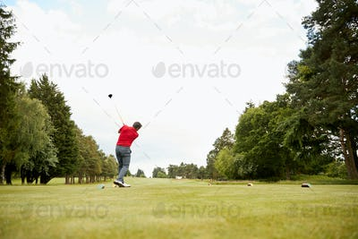 Mature Male Golfer Hitting Tee Shot Along Fairway With Driver