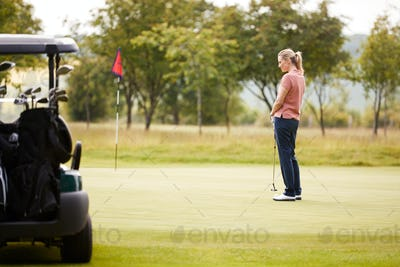 Rear View Of Woman Getting Out Of Golf Buggy To Play Shot On Green