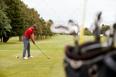 Mature Male Golfer Preparing To Hit Tee Shot Along Fairway With Bag Of Clubs In Foreground