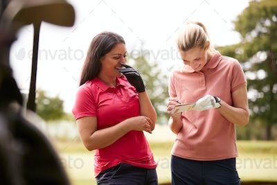 Two Women Playing Golf Marking Scorecard With  Buggy In Foreground