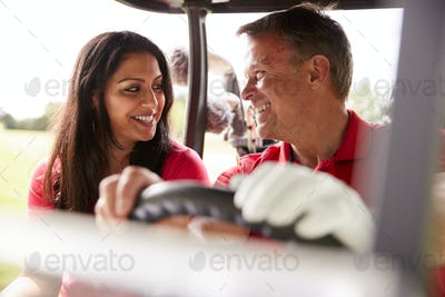 Mature Couple Playing Golf Driving Buggy Along Course To Green On Red Letter Day