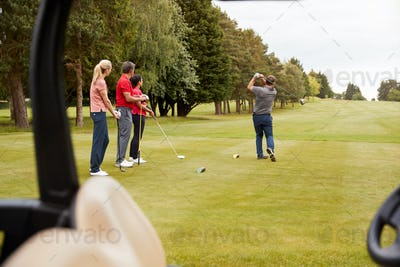 Two Couples Golfing Hitting Tee Shot Along Fairway With Driver With Buggy In Foreground