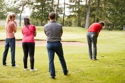 Golf Professional Demonstrating Shot On Fairway To Group Of Golfers During Lesson