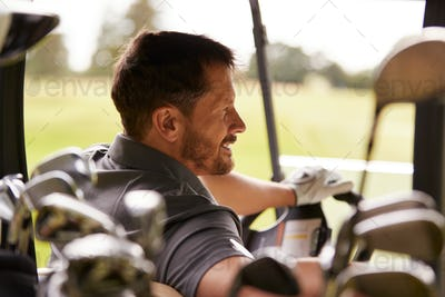 Rear View Of Mature Man Playing Golf Driving Buggy Along Course Viewed Through Golf Clubs