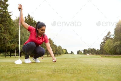 Female Golfer Preparing To Hit Tee Shot Along Fairway With Driver