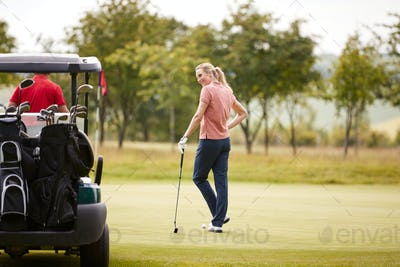 Rear View Of Couple Getting Out Of Golf Buggy To Play Shot On Green