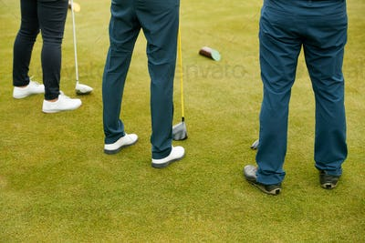Close Up Of Legs Of Golfers Holding Clubs On Golf Tee