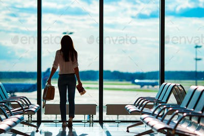 Young woman in international airport with her luggage background big window. Airline passenger in an