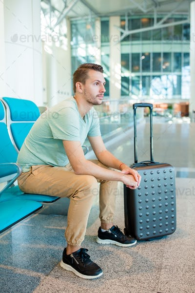 Young man in an airport lounge waiting for flight aircraft