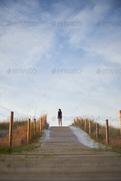 Young woman on the top of a dune on Vao beach in Vigo, Spain