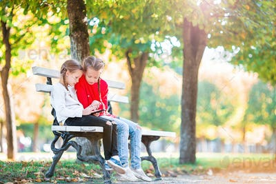 Little adorable girls with smartphone in fall outdoors. Kids having fun at warm sunny day in autumn