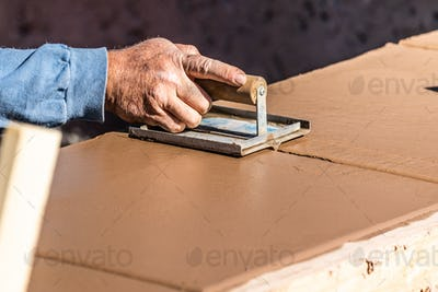 Construction Worker Using Hand Groover On Wet Cement Forming Coping Around New Pool