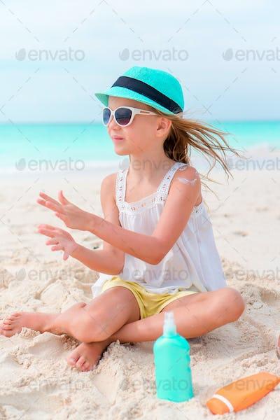 Little girl with bottle of sun cream