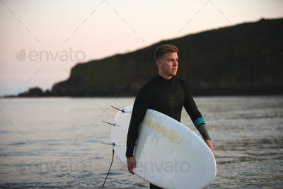 Man Wearing Wetsuit Carrying Surfboard As He Walks Out Of Sea