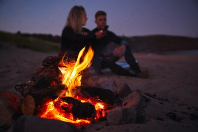 Couple Sitting On Surfboard By Camp Fire On Beach Using Mobile Phone As Sun Sets Behind Them