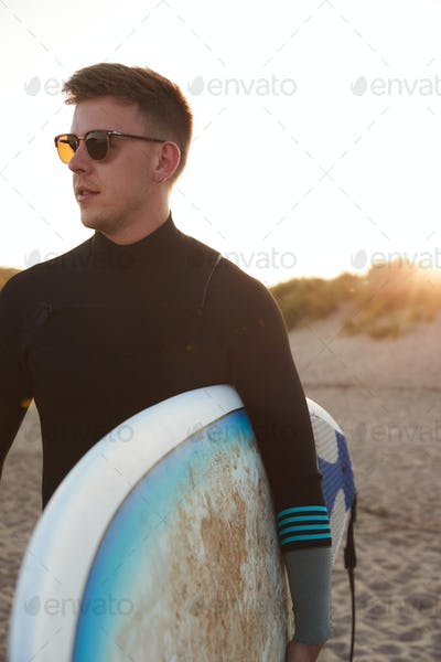 Young Man In Sunglasses Wearing Wetsuit Enjoying Surfing Staycation On Beach As Sun Sets
